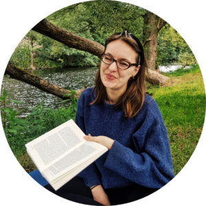 A photo of me sitting besides a river. I am wearing a blue pullover and holding a book.
